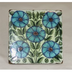 William De Morgan tile decorated with five flower heads. Stamped DM98. Circa 1880