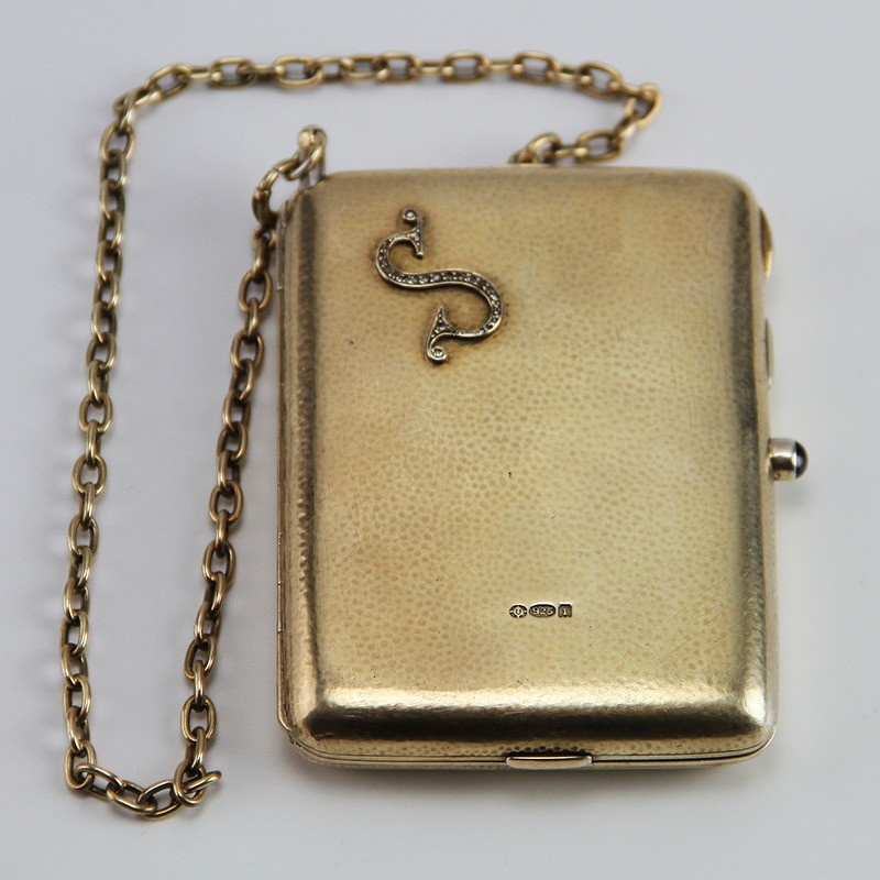 London 1906 in silver gilt. Set with a letter S encrusted with diamonds, and a sapphire cabochon set into the clasp.