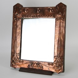 Antique Arts and Crafts copper mirror with raised arrow-topped details and embossed floral design (c.1900)