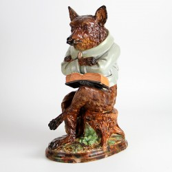 Wayte & Ridge Longton Staffordshire Majolica figure of a seated fox with crossed legs and arms balancing a book (c.1880)