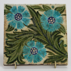 Antique William De Morgan tile with three blue flower heads and green foliage. (c.1890)